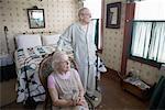 Portrait of feeble senior couple in bedroom