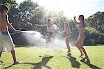 Teenage boy spraying teenage girls with hose outdoors