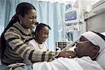 Nahaufnahme eines jungen auf einem Krankenhausbett liegen und bei seiner Mutter und seiner Schwester lächelnd