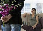 Vue arrière d'une femme souriante à un homme tenant des fleurs dans le dos