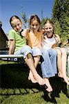 Portrait of three girls sitting on a trampoline