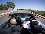 Vue arrière d'un couple de jeunes mariés dans une voiture