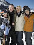 Porträt von wenigen Mitte Erwachsenen und ihre Kinder halten Ski