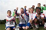 Équipe de soccer avec les médailles d'or et trophée