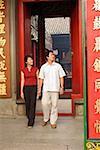 Couple holding hands walking through doorway