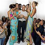Models surrounding fashion designer on catwalk after fashion show