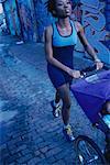 Woman jogging along city street, pushing three-wheeled baby carriage