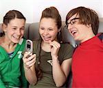 Drei Jugendliche (13-15) Blick auf Handy, lachen