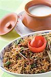 Nahaufnahme einer Schale gebratenen Reis mit einer Schüssel Quark auf einen Teller