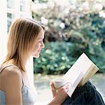 Junge Frau, lesen, halten Cup lächelnd