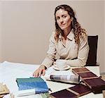 Woman sitting at desk in office, portrait