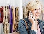 Junge Frau mit Handy im Bekleidungsgeschäft, Lächeln, close-up