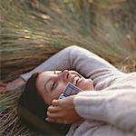 Junge Frau liegend auf Gras mit Handy, lächelnd, Nahaufnahme