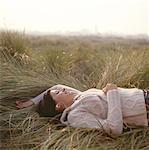 Junge Frau liegend auf Gras tragen Kopfhörer, Augen geschlossen, seitliche Ansicht