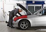 Mature mechanic working under car bonnet in garage, side view