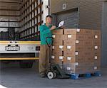 Homme écrit sur papier à côté de boîtes sur transpalette, camion