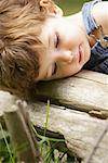 Little Boy Resting Head on Log