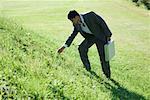 Homme d'affaires permanent de colline herbeuse, plier vers le bas pour toucher l'herbe
