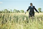 Homme d'affaires permanent en champ, bras tendus, la tête en arrière et les yeux fermés