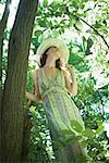 Junge Frau tragen Sommerkleid und Sonnenhut, ständigen nächsten Baum, low Angle view