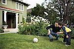Père et fils, jouer au Soccer sur la pelouse