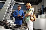 Frau und Mechaniker suchen unter Auto-Haube