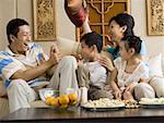 Famille ayant pillow fight sur canapé en riant