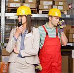 Businesswoman and worker talking on walkietalkies
