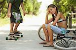 Little Girl Sitting on Bike, Boy Skateboarding