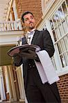 Butler in front of mansion