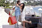 Woman embracing man holding shopping bags