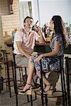 Couple in a bar, man smoking cigar