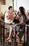 Couple in a bar, man lighting cigar