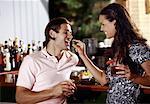 Woman feeding man in a bar