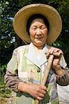 Femme avec chapeau de paille et souriant de pelle debout à l'extérieur