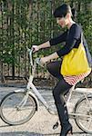Jeune femme assise sur une bicyclette sur le trottoir