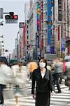 Businesswoman standing near pedestrian crossing on busy street wearing pollution mask, Tokyo, Japan
