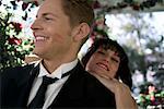 Mariée debout derrière marié avec une marque de rouge à lèvres sur sa joue