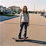 Teenage girl standing on skateboard in the street