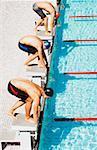 Three swimmers on pool start blocks
