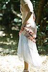 Junge Frau im Wald stehend heben Rock, beschnitten, Seitenansicht