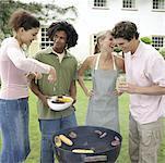 Vier Personen mit Grill im Garten