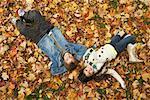 Children Lying in Autumn Leaves