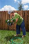 Profil de côté d'une femme senior planter une plante