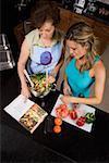 Vue grand angle d'une jeune femme, préparation de la nourriture avec sa mère dans la cuisine