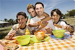 Deux garçons, manger des saucisses avec leurs parents dans un pique-nique