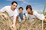 Milieu adulte couple avec leur fils jouent sur la plage