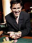 Gros plan d'un jeune homme acclamant avec poignée de copeaux dans un casino de jeu