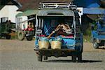 Passenger traveling in a jinrikisha, Vang Vieng, Laos