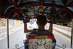 Rear view of a man driving a tuk- tuk, Bangkok, Thailand